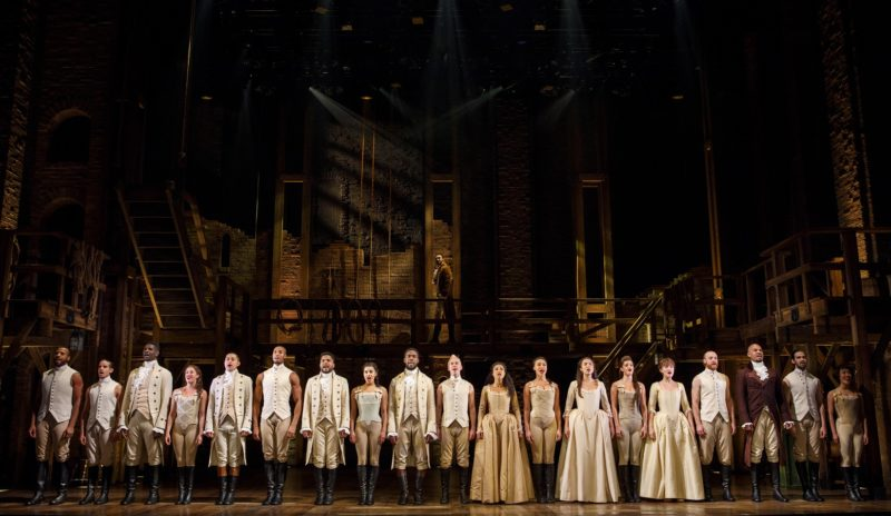 "The entire cast stands shoulder to shoulder in the front while Alexander Hamilton walks by in the background in the opening song ""Alexander Hamilton."""