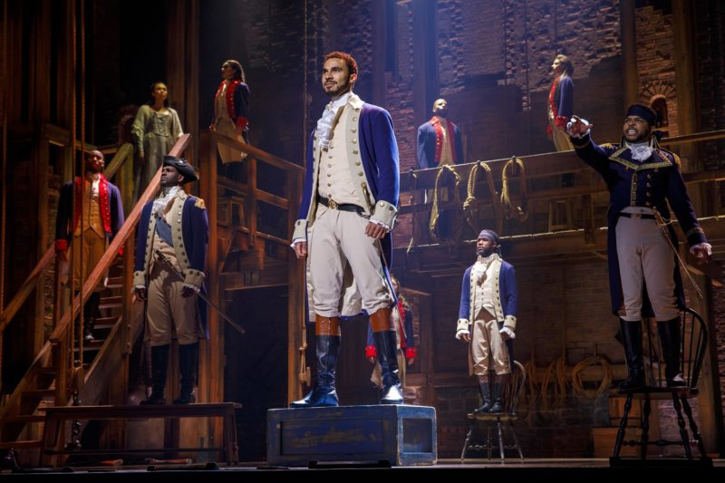 Alexander Hamilton, General George Washington, Hercules Mulligan and the Marquis de Lafayette watch as the British army surrenders.
