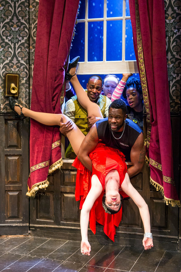 4 actors outside of a window grasp at the actress who has just fainted and is now dangling upside down.